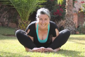 Louise sitting on grass in lotus pose smiling