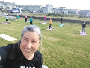 Yoga teacher and class outside in Waterville