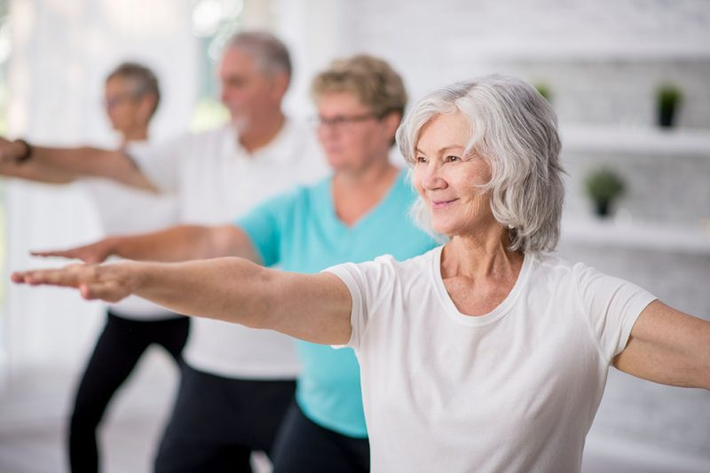 4 older people doing a standing yoga pose with arms outstretched. The woman at the front has white hair and is smiling.