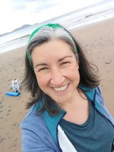 Close up of a smiling Louise on a beach wearing a green hairband